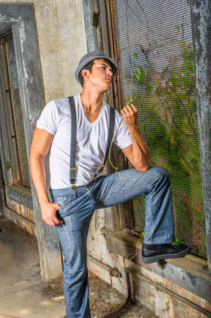 Dressing in a white T shirt, blue jeans with suspenders, and a gray fedora hat,  a young handsome guy is standing by a screen window inside a abandoned house,  looking at green leaves and into deeply thinking. Stockfoto