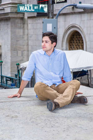 A young handsome guy is sitting on a stage in the corner of the street, relaxing and thinking. There is a Wall Street sign in the background. Stockfoto