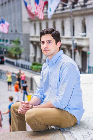 Clamping his hands, a young handsome guy is sitting outside on a stage into deeply thinking. There are American flags hanging on buildings in the background. Stockfoto
