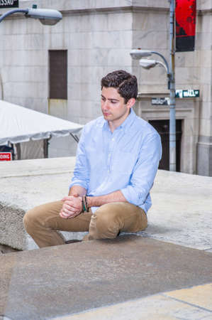 Clamping his hands and lowering his head, a young handsome guy is sitting on a stage in the corner of the street, relaxing and thinking. Stockfoto