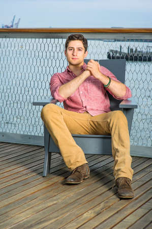 Dressing in a light red shirt, dark yellow pants and brown shoes, a young handsome guy is sitting on a chair in the deck by the river, clutching hands,  relaxing.