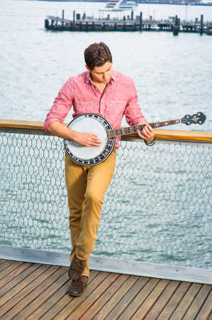 Dressing in light red shirt, dark yellow trousers and brown shoes, hanging his head and stepping his foot, a young musician is playing a banjo on the deck