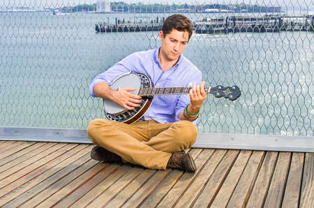 Lowering his head, crossing legs  and thinking,  a young musician is sitting on the deck, playing a banjo