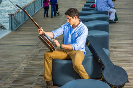 Dressing in a light blue shirt, dark yellow jeans and brown boot shoes, a young musician is sitting on a modern style bench, tuning strings of a banjo. Stockfoto