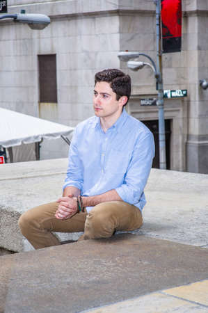 Clamping his hands and looking forward, a young handsome guy is sitting on a stage in the corner of the street, relaxing and thinking. Stockfoto