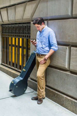 Dressing in a light blue shirt, dark yellow pants and brown shoes, a young musician with a instrument box is standing on the street and leaning against the wall, busily  checking messages on his mobile phone. Stockfoto