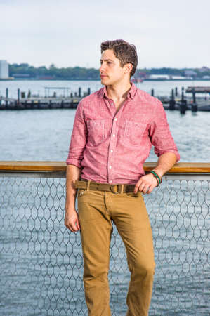 Dressing in a light red shirt, dark yellow pants, a young handsome guy is standing by the river, looking forward and waiting for you. Stockfoto