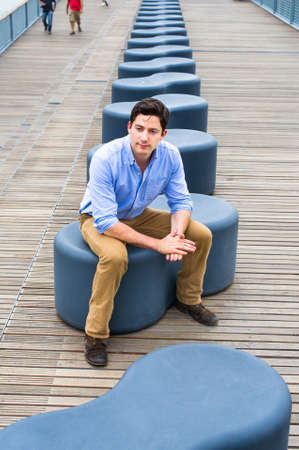 Dressing in a light blue shirt, dark yellow jeans and brown boot shoes, a young handsome guy is sitting on a modern style bench, relaxing and thinking.