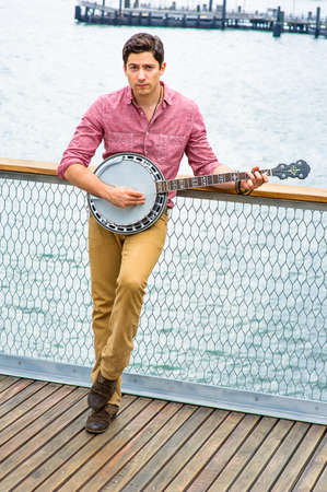 Dressing in light red shirt, dark yellow trousers and brown shoes, looking up and stepping his foot, a young musician is playing a banjo on the deck
