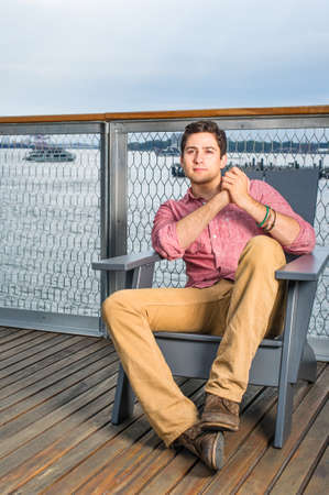 Dressing in a light red shirt, dark yellow pants and brown shoes, a young handsome guy is sitting on a chair in the deck by the river, clutching hands, stepping foot,  relaxing. Stockfoto