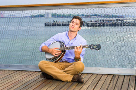Against a fence, looking up, crossing legs  and thinking,  a young musician is sitting on the deck, playing a banjo