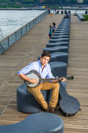 Dressing in a light blue shirt, dark yellow jeans and brown boot shoes, a young musician with an instrument box is sitting on a modern style bench, playing a banjo.