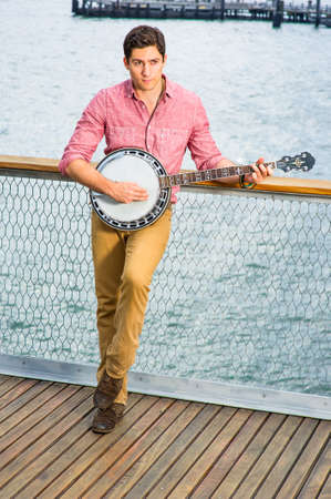 Dressing in light red shirt, dark yellow pants and brown boot shoes, looking up and stepping his foot, a young musician is playing a banjo on the deck