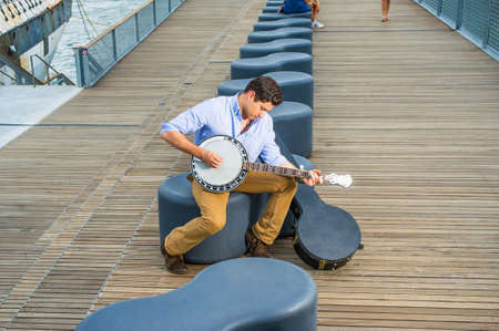 Dressing in a light blue shirt, dark yellow jeans and brown boot shoes, a young musician with an instrument box is sitting on a modern style bench, lowering his head and playing a banjo.