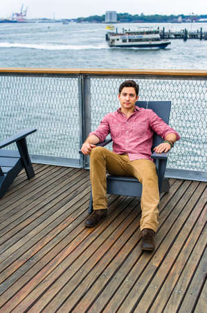 Dressing in a light red shirt, dark yellow pants and brown shoes, a young handsome guy is sitting on a chair in the deck by the river, relaxing. There is a small boat in the background.