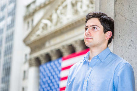 A young guy is sincerely looking forward. There is American flag in the background.