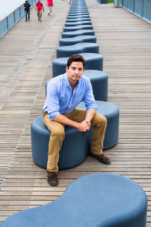 Dressing in a light blue shirt, dark yellow jeans and brown boot shoes, a young handsome guy is sitting on a modern style bench, charmingly looking at you. Stockfoto