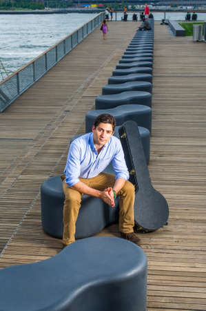 Dressing in a light blue shirt, dark yellow jeans and brown boot shoes, a young handsome musician with a music instrument box is sitting on a modern style bench in the evening, charmingly looking at you.