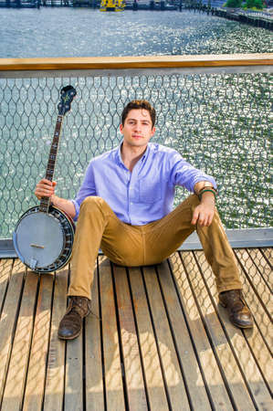 Dressing in a light blue shirt, dark yellow jeans and brown boot shoes, holding a banjo, a young musician is sitting on the deck against a fence, relaxing