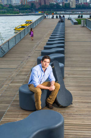 Dressing in a light blue shirt, dark yellow jeans and brown boot shoes, a young handsome musician with a instrument box is sitting on a modern style bench in the evening, charmingly looking at you.