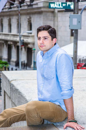 Shrugging his shoulder, a young handsome guy is sitting outside on a stage to relax. There is a Wall Street sign in the background.