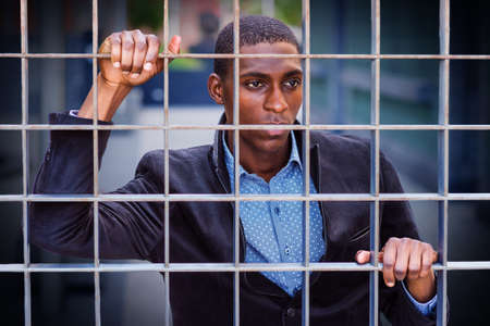 Concept of Looking for Freedom. A young African American man is passionately looking through the metal fence, thinking, lost in thought.