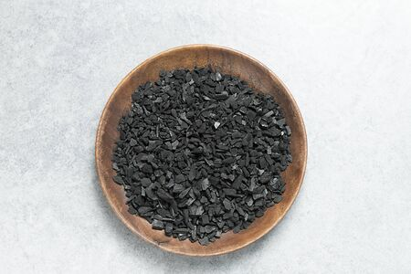Activated carbon on a wooden plate Stock fotó