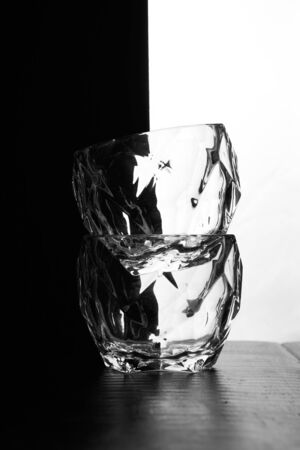 glasses of whiskey lie on top of each other. There's a bottle of whiskey next to me. Black white background. Silhouettes. High quality photo