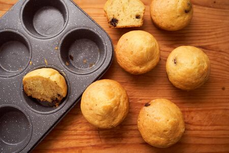 Homemade cupcakes lie on a wooden plate. Closeup