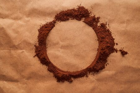 A circle of ground coffee on a brown background. Place to insert a slogan or text. High quality photo