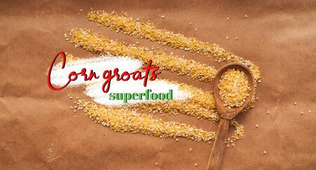 Corn grits scattered on a cherrymeal background with a wooden spoon. High quality photo
