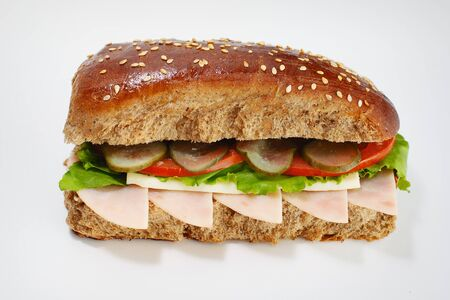 Juicy sandwich from dark flour with cucumbers, lettuce, cheese and ham on a white background. High quality photo