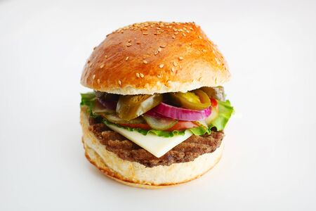 Juicy burger with onion rings, jalapeno pepper, cucumbers, lettuce, cheese on a white background. High quality photo