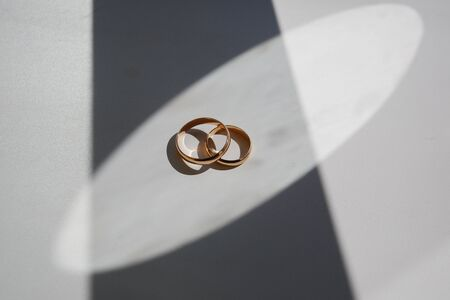 Wedding rings lie on a white background. Game of Shadows . High quality photo