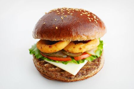 Juicy burger from dark flour with onion rings, cucumbers, lettuce, cheese on a white background. High quality photo