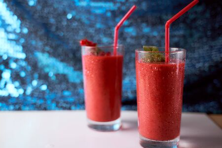 Strawberry and banana smoothies with long glasses on white plate. Blue background. High quality photo