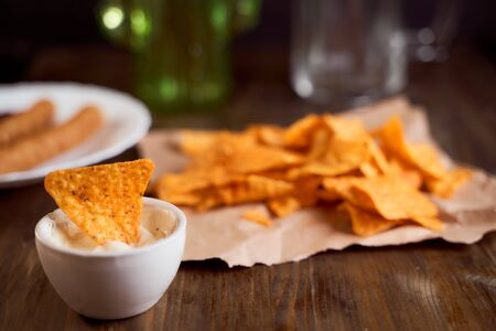 Mexican corn chips nachos lie on a wooden table. One thing in a bowl with sauce. High quality photo