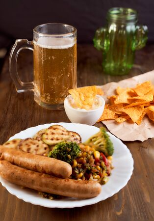 Grilled vegetables with sausage and Mexican corn chips nachos, light beer lie on a wooden table. One thing in a bowl with sauce. High quality photo Reklamní fotografie