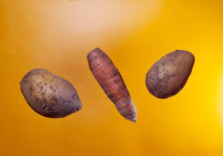Not beautiful potatoes and carrots on an orange background. Isolate. High quality photo