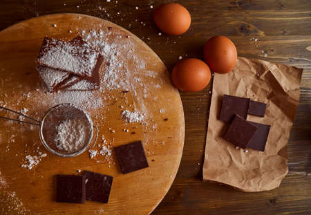 Composition of Chocolate cakes stacked on a wooden table. next to it are eggs and pieces of chocolate. Top view. High quality photo
