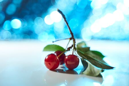 Cherry on a white background with blue highlights and shadows. Close-up. Top view.. High quality photo