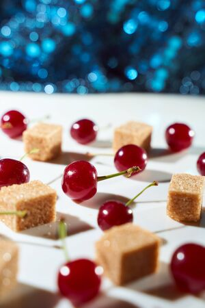 Group of cherry on a white background with cubes of reed sugar and shadows. Close-up. Top view. High quality photo