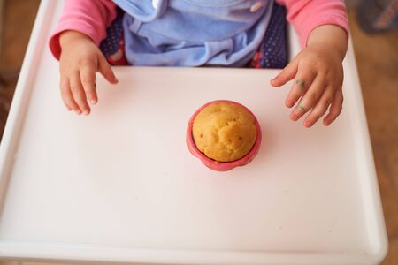 A child holds a homemade cupcake sitting at a table. High quality photo