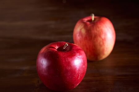 two red apples lie on a cinnamon wooden table. High quality photo