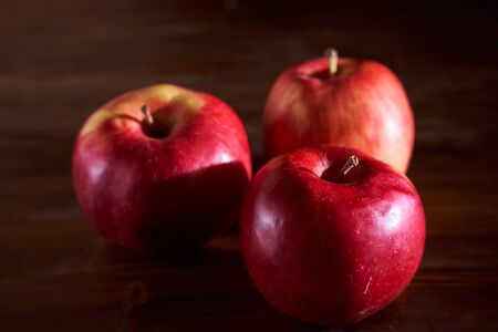 Three red apples lie on a cinnamon wooden table. High quality photo