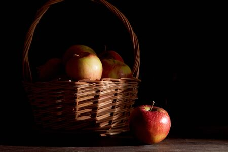 Braided basket with red apples on a black background. High quality photo 免版税图像