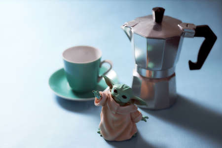12.07.2020 Baby Yoda and geyser coffee maker stands on a blue background. With copy space.