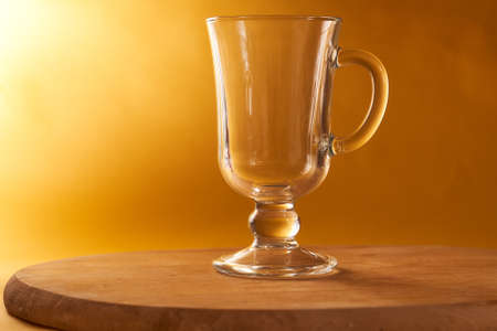 Glass goblet stands on a wooden board on a yellow background. High quality photo