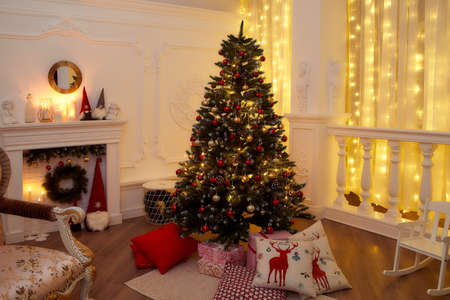 New Years interior with Christmas tree, fireplace, pillows. Very beautiful evening photo for Christmas
