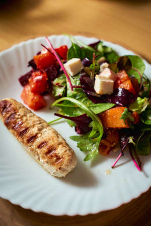 Vegetable salad with beetroot and pumpkin on a white plate with grilled chicken sausage. Vertical orientation.